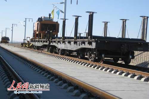 铺轨作业车将两条长500米钢轨缓缓铺设在双块式无砟轨道轨枕