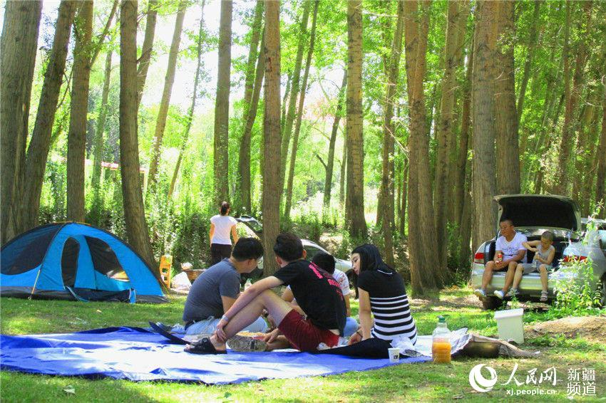 8月3日,新疆塔城市民在城郊河道的树林中休闲避暑。五条河流穿城而过的新疆塔城市有五弦之都美称,是全疆空气质量最好的城市,夏季持续的高温天气也催热了新疆塔城市民的生态休闲游,塔城人在这巨大的露天空调里尽情享受着炎热夏日里的清凉。(通讯员 杨化光)