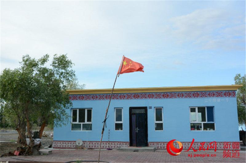 蓝色的房屋边沿雕琢着哈萨克族风格的花纹,远处的雪山映衬着落日的