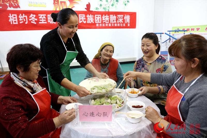 """社区干部和""""民族团结一家亲""""结对亲戚、各族居民一起吃饺子。"""