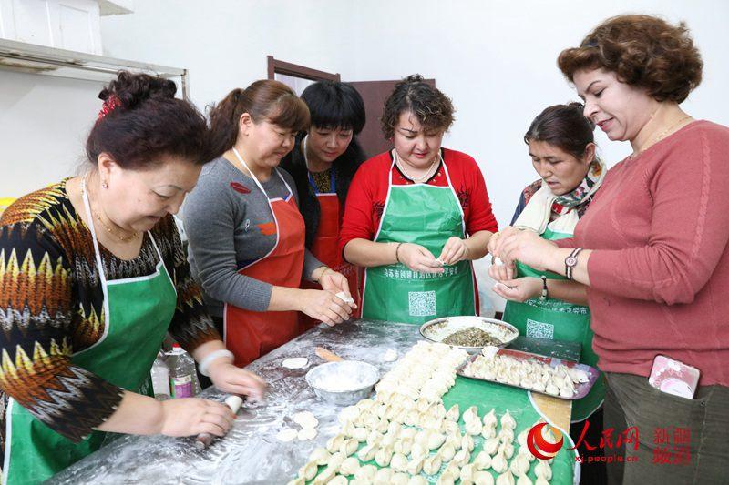 """社区干部和""""民族团结一家亲""""结对亲戚、各族居民一起包饺子。"""