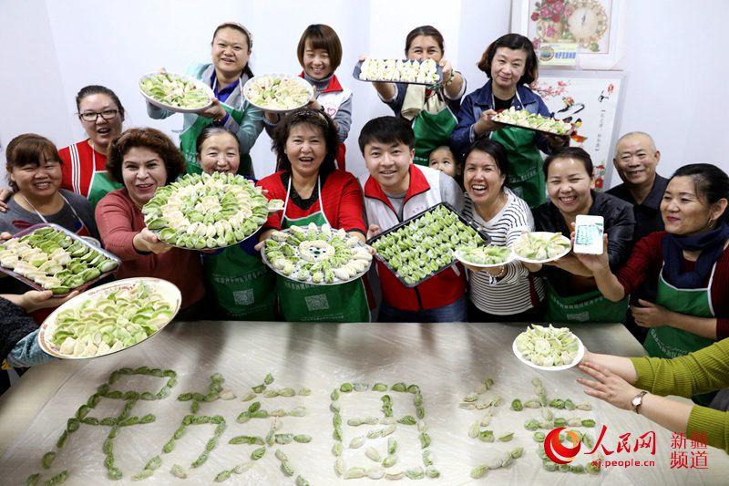 """社区干部和""""民族团结一家亲""""结对亲戚、各族居民与包好的饺子合影。"""